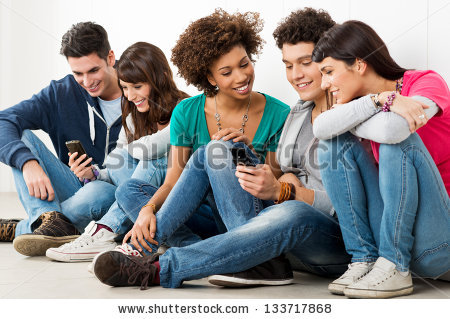 stock-photo-group-of-happy-young-friends-looking-at-cell-phone-133717868